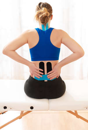 Female patient with kinesio tape on her lower back sitting on an examination table, rear view. Kinesiology, physical therapy, rehabilitation concept.