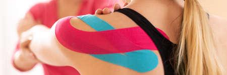 Kinesiologia, terapia fisica, banner di riabilitazione. Paziente di sesso femminile che indossa nastro kinesio sulla spalla che si esercita con un fisioterapista professionista. Avvicinamento. Archivio Fotografico