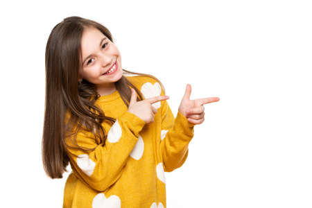 Beautiful young girl in mustard yellow sweater looking at camera, smiling and pointing to the side. Waist up studio shot on white background.