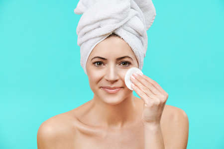Smiling mid adult woman removing make up using a cotton pad. Photo of an attractive caucasian woman with healthy skin isolated on turquoise background. Beauty and Skincare concept.