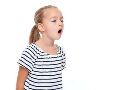 Cute little girl in stripped T-shirt talking. Speech therapy concept over white background.