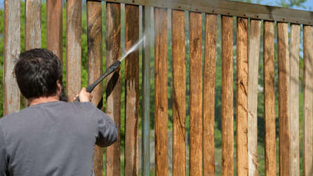 Unrecognizable man cleaning a wooden gate with a power washer.
