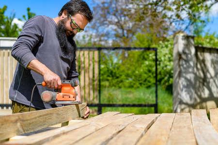 Mid adult caucasian man in the garden sanding wooden planks. DIY home improvement, restoration, carpentry concept.