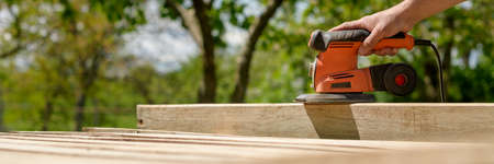 Unrecognizable man in the garden sanding wooden planks. DIY home improvement, restoration, carpentry concept. Hand detail banner with copy space. 版權商用圖片