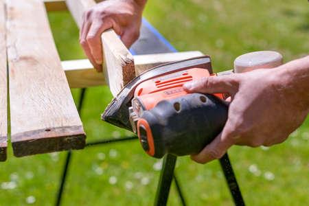 Unrecognizable man in the garden sanding wooden planks. DIY home improvement, restoration, carpentry concept. Hand detail shot.