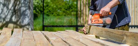 Unrecognizable man in the garden sanding wooden planks. DIY home improvement, restoration, carpentry concept. Midsection banner with copy space.