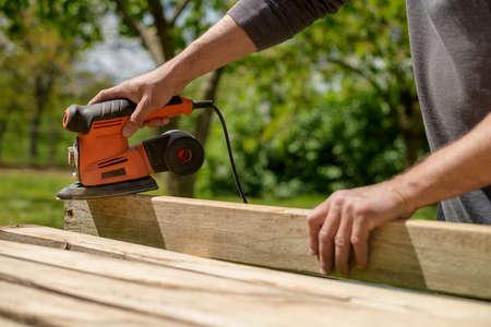 Unrecognizable man in the garden sanding wooden planks. DIY home improvement, restoration, carpentry concept. Midsection hand detail shot. 版權商用圖片