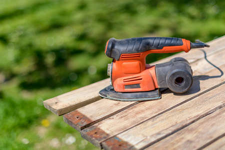 Wood sanding in the garden. DIY home improvement, restoration, carpentry concept. Close up shot of an electric sander on wooden planks.
