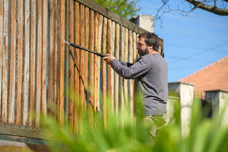 Mid adult man cleaning a wooden gate with a power washer. High water pressure cleaner used to DIY repair garden gate. Standard-Bild
