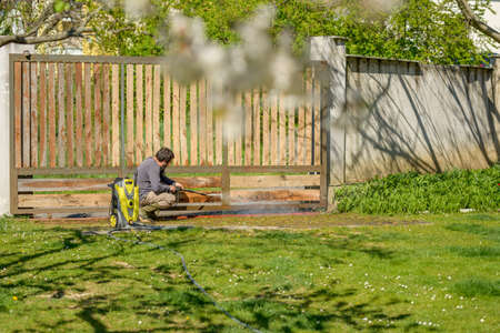 Mid adult man cleaning a wooden gate with a power washer. High water pressure cleaner used to DIY repair garden gate. 版權商用圖片