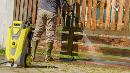 Unrecognizable man cleaning a wooden gate with a power washer. High water pressure cleaner  used to DIY repair garden gate. 版權商用圖片