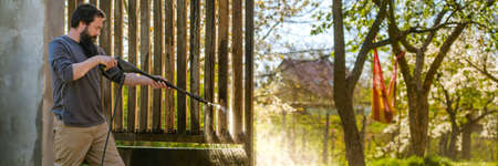 Mid adult caucasian man cleaning a wooden gate with a power washer. High pressure water cleaner used to DIY repair garden gate. Web banner. Standard-Bild
