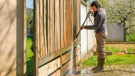 Mid adult man cleaning a wooden gate with a power washer. High pressure water cleaner used to DIY repair garden gate.