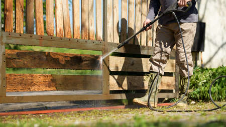Unrecognizable man cleaning a wooden gate with a power washer. High water pressure cleaner  used to DIY repair garden gate. Standard-Bild