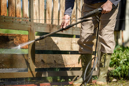 Unrecognizable man cleaning a wooden gate with a power washer. High water pressure cleaner  used to DIY repair garden gate. Фото со стока
