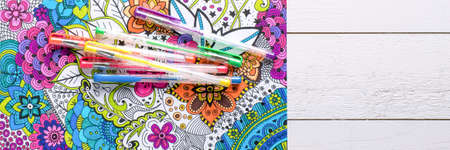 Adult coloring book, stress relieving trend. Art therapy, mental health, creativity and mindfulness concept. Flat lay web banner, panoramic close up shot.