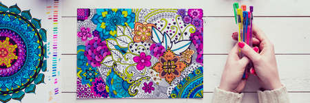 Adult coloring book, stress relieving trend. Art therapy, mental health, creativity and mindfulness concept. Flat lay close up on woman hands coloring an adult coloring book banner. 版權商用圖片