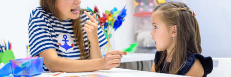 Children speech therapy concept. Preschooler practicing correct pronunciation with a female speech therapist. Web banner.