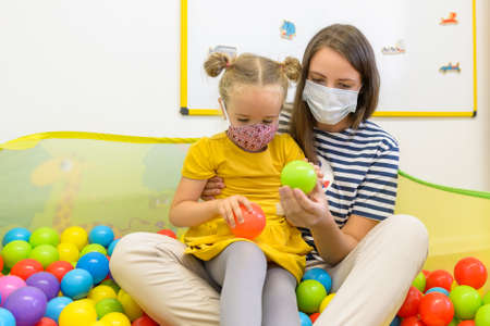 Toddler girl in child occupational therapy session doing playful exercises with her therapist during Covid - 19 pandemic, both wearing protective face masks. Archivio Fotografico