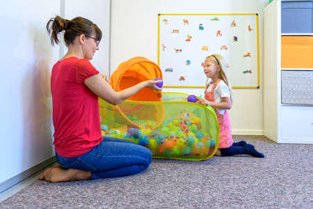 Toddler girl in child occupational therapy session doing playful exercises with her therapist.