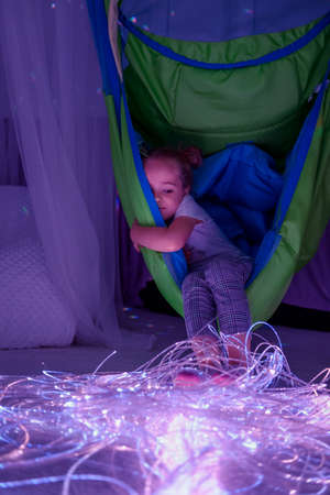 Child in therapy sensory stimulating room, snoezelen. Autistic child interacting with colored lights during therapy session. 版權商用圖片