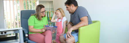 Father and preschooler daughter in therapist office during counselling assessment meeting. Social worker talking to single father during interview. Web banner.