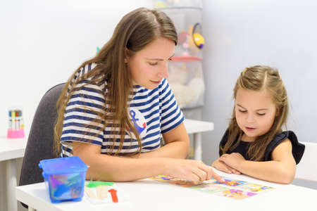 Children speech therapy concept. Preschooler practicing correct pronunciation with a female speech therapist.