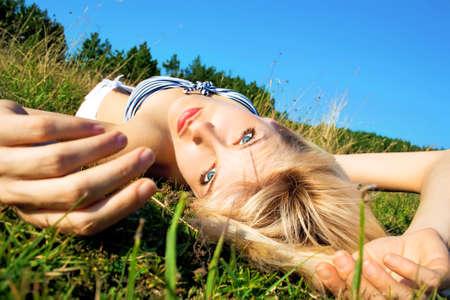 woman lying down: young beautiful woman lying down on grass