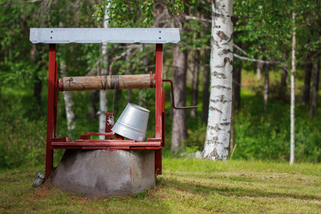 Water well painted in red and a resting tin bucket