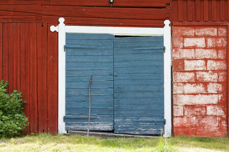 Red painted barn with two blue painted doors photo