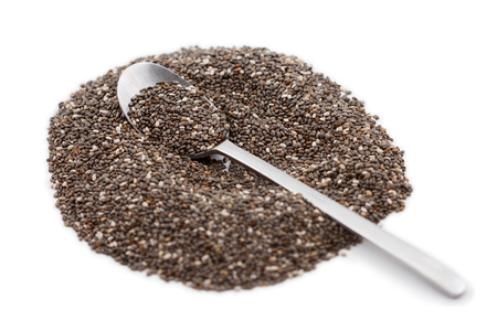 Heap of chia seeds and spoon isolated on white