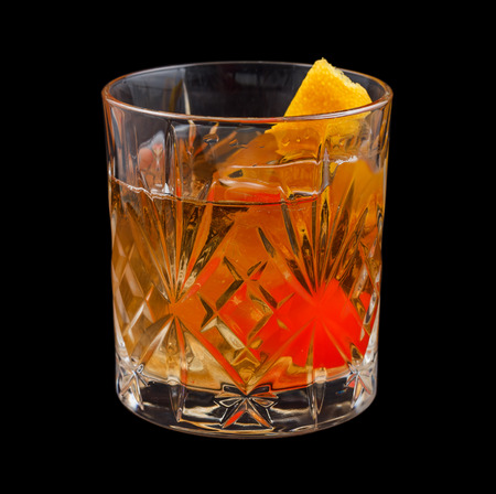 Old Fashioned drink, consisting of bourbon, sugar cube, angostura bitters and soda water. Isolated on black background