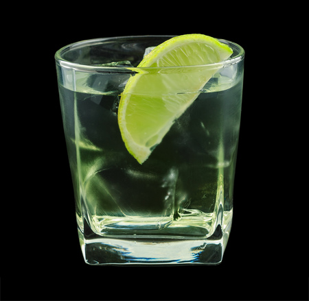 cordial: Vodka lime is a cocktail that contains vodka, lime cordial and is garnished with a lime wedge. Isolated on black. Stock Photo