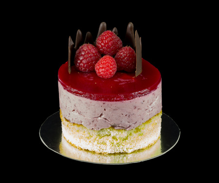 small cake: One small cake with chocolate and raspberries isolated on black