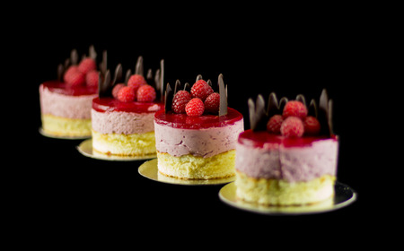 chocolate mousse: Four small cakes with chocolate and raspberries isolated on black