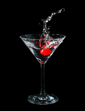 distilled water: Maraschino cherry dropped in cocktail glass with fluid isolated on black Stock Photo
