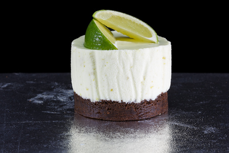 small cake: One small cake decorated with lime wedges isolated on black