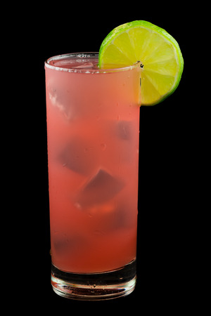 Bay of Passion a pink drink that contains vodka cranberry juice pineapple juicepassion fruit liqueur and garnished with a slice of lime. Isolated on black.