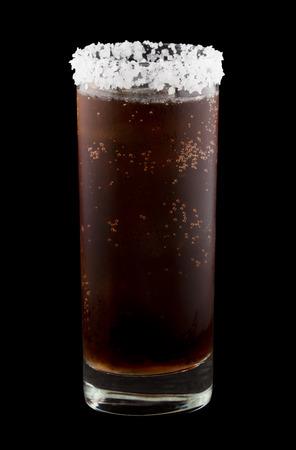 rimmed: Batanga es una bebida mexicana que contiene tequila y refresco de cola y est� bordeado con sal. Aislados en negro.