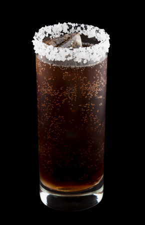 black rimmed: Batanga is a Mexican drink that contains tequila and cola and is rimmed with salt. Isolated on black. Stock Photo