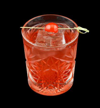 grenadine: Red drink that contains vodka, rose syrup, grenadine and cranberry juice and is garnished with a maraschino cherry. Isolated on black.