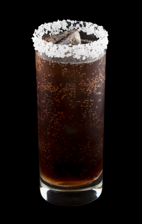 rimmed: Batanga is a Mexican drink that contains tequila and cola and is rimmed with salt. Isolated on black. Stock Photo