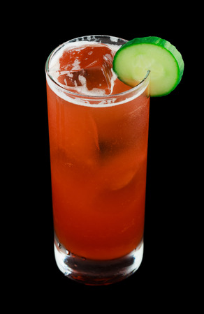 ambrosia: Drink called Ambrosia Swizzle that contains rum, vanilla liqueur, strawberries, cucumber, pineapple juice, lime juice, simple syrup and bitters. Garnished with a cucumber slice. Isolated on black.