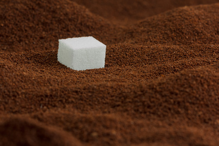 sugar cube: Sugar cube in lots of ground coffee looking like valleys and mountains Stock Photo