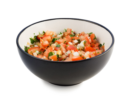 The traditional Mexican cuisine pico de gallo in a black bowl isolated on white