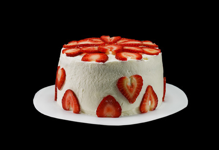 One white cake decorated with slices of strawberries isolated on black