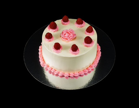 One white cake decorated with rose and raspbarries isolated on black