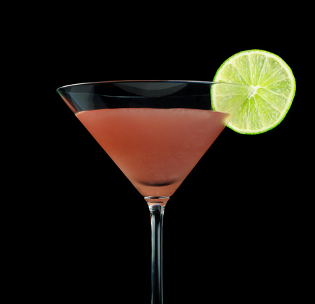 Cosmopolitan cocktail, consisting of lemon vodka, triple sec, cranberry juice and freshly squeezed lime. Garnished with a slice if lime. Isolated on black background.
