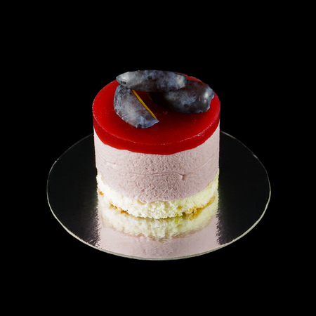 One small cake decorated with plum wedges isolated on black Standard-Bild