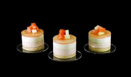 Three small cake decorated with different fruits isolated on black